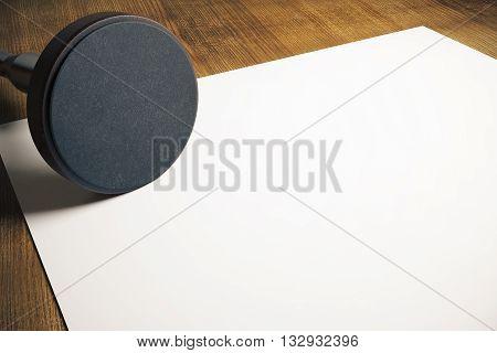 Round stamper and blank paper sheet on wooden desktop. Mock up 3D Rendering