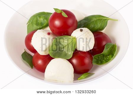 Round camembert cheese with cherry tomatoes and basil on a white plate.