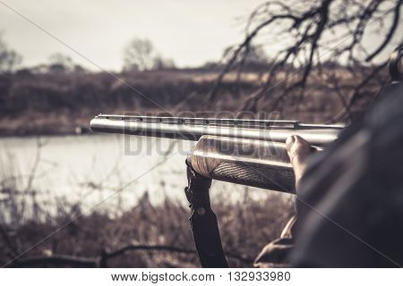 Gun barrel ready to shot during duck hunting season on river bank in overcast day