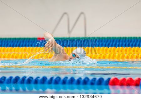 Man swimmer swimming crawl in blue water. Portrait of an athletic young male triathlete swimming crawl wearing a gray cap and swimming goggles while. Triathlete training for triathlon.