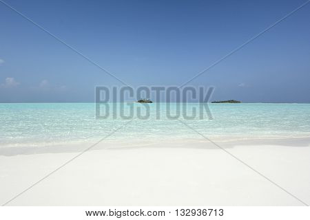 small maldivian islands in turquise water with white sand