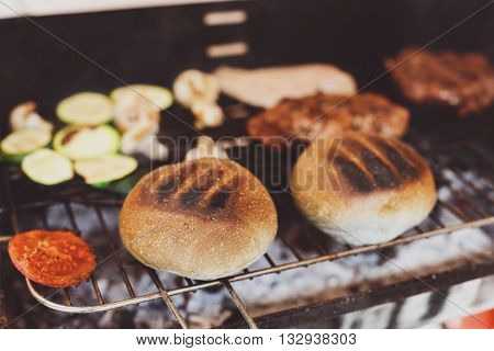 Barbecue grill outdoors. Cookout american bbq food. Big burger roasted buns, pork and beef steak meat, mushrooms, tomato. Street food, fast food.