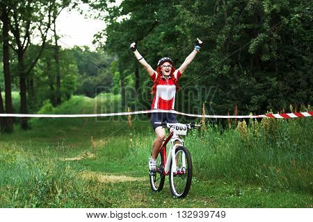 Crossing the line. Winner. Victory moment. Young red-haired woman cyclist in protective helmet crossing the finish line breaking the tape. Win the cycling race. Bicycle sport.
