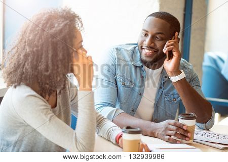 Be reachable all time. Smiling and happy modern young people sitting in a cafe and drinking coffee while talking on their mobile phones