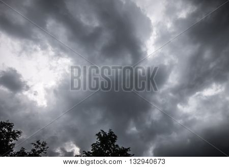 Dark thunderclouds over dark trees in summer