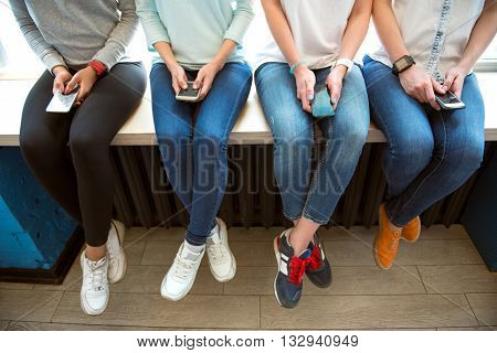 Using mobile phones. Cropped picture of four modern young women using their mobile phones while sitting on a window sill