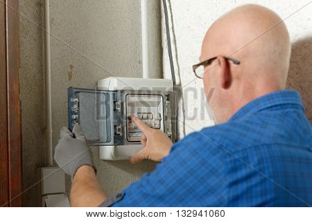 a mature man working with electric box at house