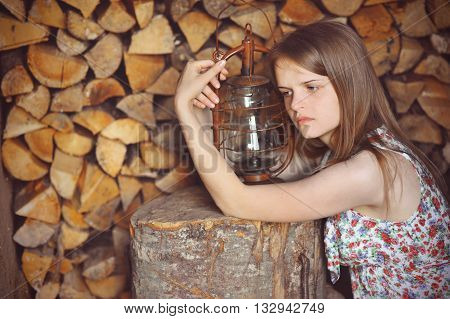 romantic sad girl with a gas lamp in the background woodpile