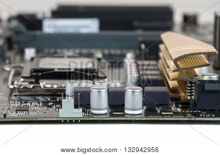 Closeup of nodern computer motherboard with capacitors and resistors
