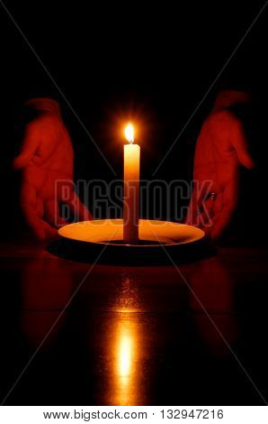Married man's hands on either side of the soft glow of a lit candle.