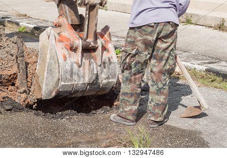 excavator scoop digging Repair of pipe water and sewerage on street Male workers repair pipe water main broken .