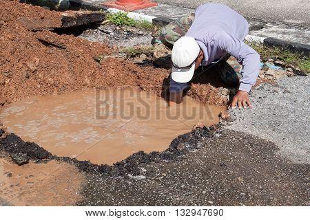 Male workers repair pipe water main broken tube underground water on road.