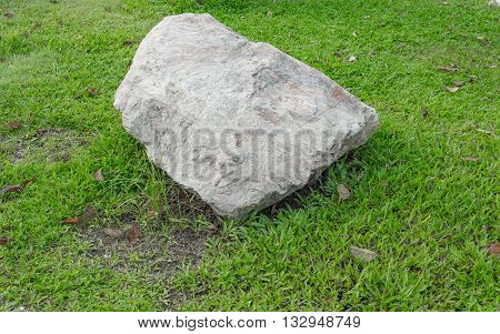 Big stone in the grass. on left of meadow in green grass . select focus stone