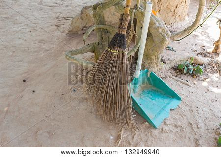 brooms coconut palms stalk on the floor soil Set of street cleaning - broom and dustpan