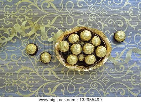 Best quality chocolates in a golden bowl on an ornamental background.
