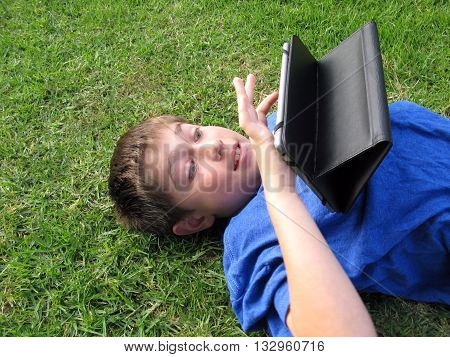 Young boy age 9 laying on grass using tablet. He has a happy expression and is wearing a blue shirt.