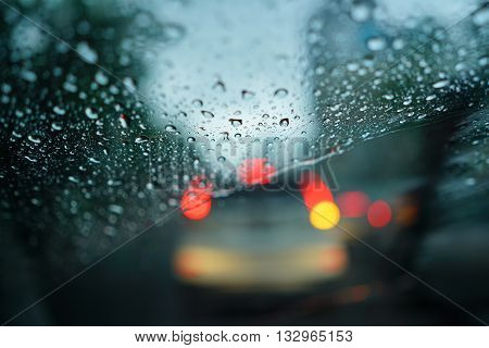 Traffic view through car window blurry with heavy rain Driving in rain