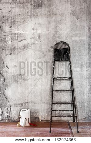 Old Dirty Concrete Wall In Repairing Room With Stepladder And Tools