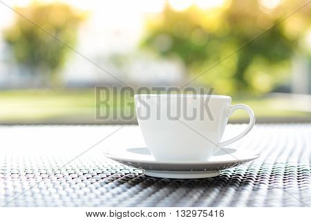 Coffee cup on the table with blurred green nature background - chill out concept