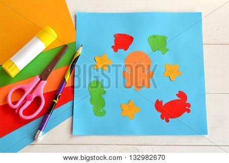 Paper sea animals on blue card. Children applique pattern. Children application. Glue stick, scissors, pencil, colored paper. Preschool and kindergarten paper crafts. DIY project.Kindergarten activity