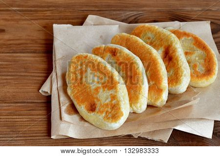 Five pies on paper and on wooden table. Fried pies with cottage cheese filling. Patties cooked on a yeast-free dough. Delicious hearty snack, breakfast, lunch. Homemade fast food. Frugal recipe idea