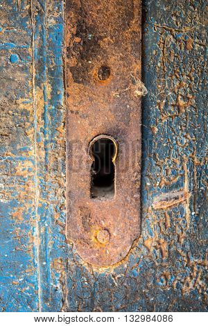 Old orange rusty keyhole iron plate on a beautiful cracked blue wooden door