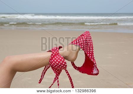 Girl On Beach Holding Bikini With Her Leg