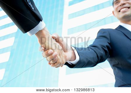 Handshake of businessmen with smiling face - greeting dealing partnership merger & acquisition concepts