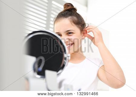 Cheerful girl assumes hearing aid viewing in the mirror