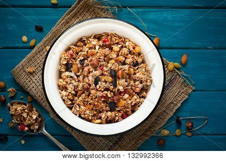 Granola and ingredients. Granola with nuts and raisins on blue wooden table.