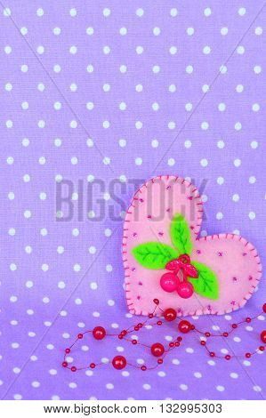 Pink felt heart with a plastic cherry, leaves and beads poster