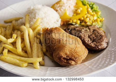 Festive menu of tasty chicken breast stuffed with ham and cheese with rice fries and pork with sauce and mushrooms. Food theme. International cuisine. Large portion.