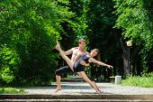 Contemporary dance. Man and woman in passionate dance pose in park. Young couple dancing modern dance. Girl doing splits. Man with naked torso. Old park, trees in background. poster