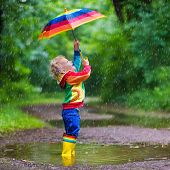 Little boy playing in rainy summer park. Child with colorful rainbow umbrella waterproof coat and boots jumping in puddle and mud in the rain. Kid walking in autumn shower. Outdoor fun by any weather poster