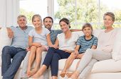 Portrait of happy family sitting on couch at home. Smiling parents, grandparents and happy children looking at camera. Portrait of extended family group sitting together. poster