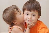Little sister kissing older brother Caucasian kids poster