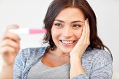 pregnancy, fertility, maternity, emotions and people concept - happy smiling woman looking at pregnancy test at home poster