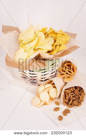 Summer Snacks - Nachos, Croutons, Chips, Tortilla In Rustic Basket And Paper Corners On White Wood B