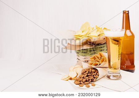Wicker Rustic Basket With Different Junk Food Snacks And Beer In Wineglasses On White Wood Backgroun