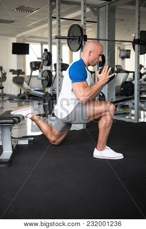 Man Athlete Exercising Glutes With Dumbbell
