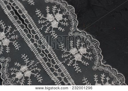 White Lace Embroidered Border On Dark Surface. Lace Texture Background On Dark Board.