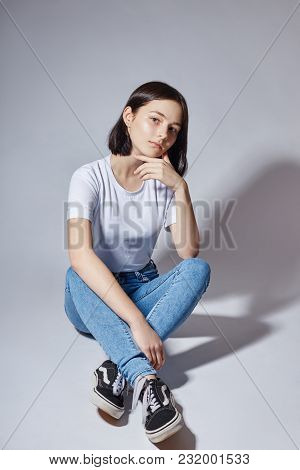 Beautiful Young Fashion Model Girl In Blue Jeans Sitting On The Floor On A White Background. Natural
