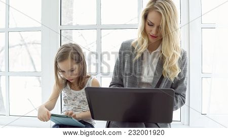 Young Business Woman With Laptop And Little Girl Are Sitting By The Window