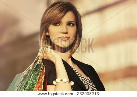 Happy young fashion woman with shopping bags at the mall. Stylish female model outdoor