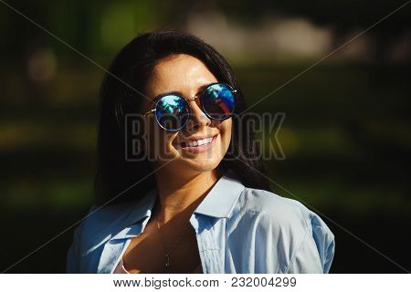 Brunette With Dazzling Smile In Sunglasses Looking At The Sun. Summer Portrait Of Cute Girl Wearing