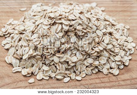 Oatmeal Or Oat Flakes On Wood Board.   Granola, Cereals Or Rolled Oats  On White Wooden Old Table. H