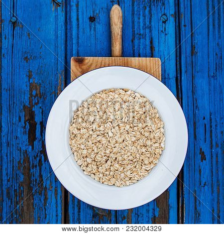Oatmeal, Rolled Oats On Colorful Blue  Background.  Food Concept Of Healthy Eating Or Vegan Food. He