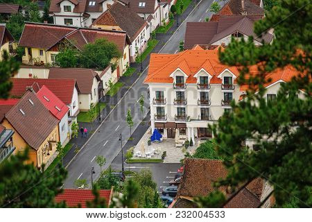 View Of The Roofs Of The Old City. Window On Tile Roof. Tile Roof On Old Building. Romania, Rasnov