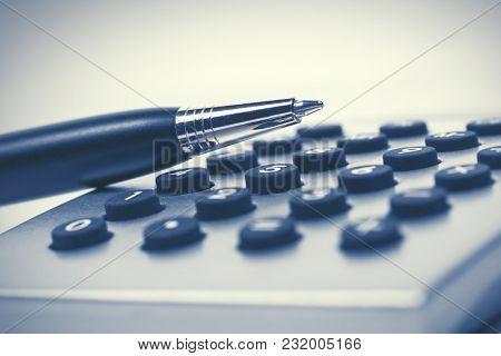 Financial accounting pen on calculator