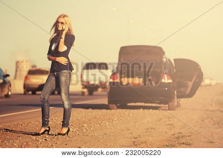 Fashion blond woman calling on cell phone next to broken car. Stylish female model in dark blue blazer and jeans outdoors